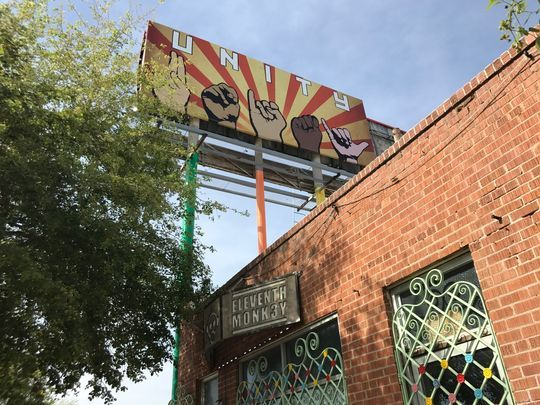 A billboard sign depicting President Donald Trump's face next to explosions and dollar signs created with typography imitating Nazi swastikas went up in downtown Phoenix ON March 17, 2017. (Photo: Johana Restrepo/The Republic).