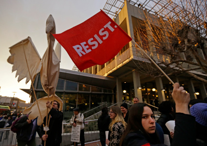 Photo of someone holding a giant dove made of cloth and sticks. Another person holds a red flag that says RESIST.