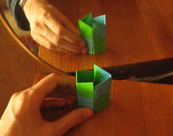 An origami arrow in front of a mirror. The arrow points to the left, while the reflection points to the right.