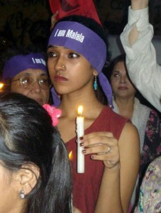 A candlelight vigil with young girls wearing purple headbands bearing the words *I AM MALALA*