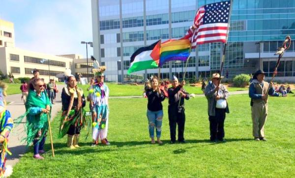 Courtesy SKINS, SFSU From L to R: Betty Parent; Ari Antone-Ramirez; Aidan Dunn Flagbearer. The Rainbow Flag is carried by Morningstar Vancil and the Eagle Staff by Edwin Gill.