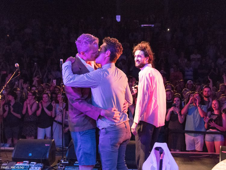 From left; Dan Mathews kisses his husband Jack Ryan on stage in Raleigh as Alex Ebert looks on; Photo courtesy of Pawel Malyszko.
