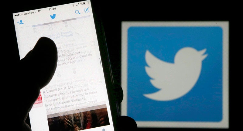 A man reads tweets on his phone in front of a displayed Twitter logo in Bordeaux, southwestern France, March 10, 2016. (REUTERS/Regis Duvignau/Illustration/File Photo)