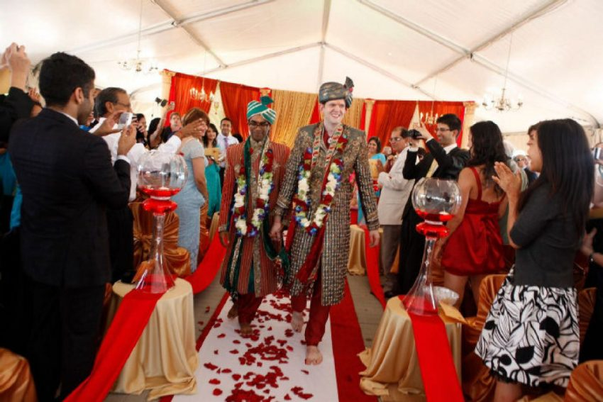 """Agarwal and Langdon are cheered after exchanging flower garlands at their wedding. """"The purpose of that is to welcome each other into each other's lives,"""" said Agarwal. """"The second that garland has been placed, it's kind of like the point of no return.""""  (Photos by Channa Photography)"""