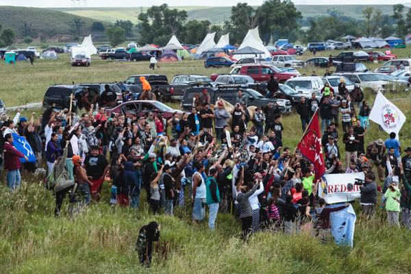 Hundreds of people lined the shores of the Cannonball River - a tributary of the Missouri river, comprising the northern border of the Standing Rock Reservation - where canoes entered the water on Saturday 8/20. (Photo: Thosh Collins)