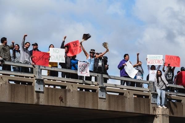 "Onlookers raise their fists in solidarity with Standing Rock and hold signs stating ""NoDAPL"" and ""Mni Wiconi."" (Photo: Thosh Collins)"