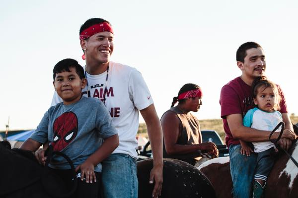Wyatt Bailey (left) and Kent St. John (right), locals from Cannon Ball, join their friends and family while riding horse through the camp, enjoying the familial and cultural spirit of activities while checking out the scene. (Photo: Thosh Collins)