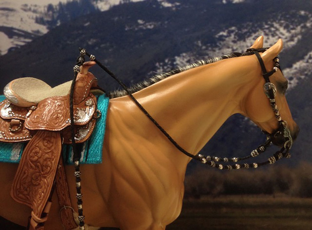 Bridle with romal reins, braided of hand cut kangaroo leather and thread, hand made sterling silver hardware. For a traditional sized model horse such as a Breyer. Horse is an artist's resin sculpture by Carol Williams, painted by Liesl Dalpe, haired by Faye Cohen.