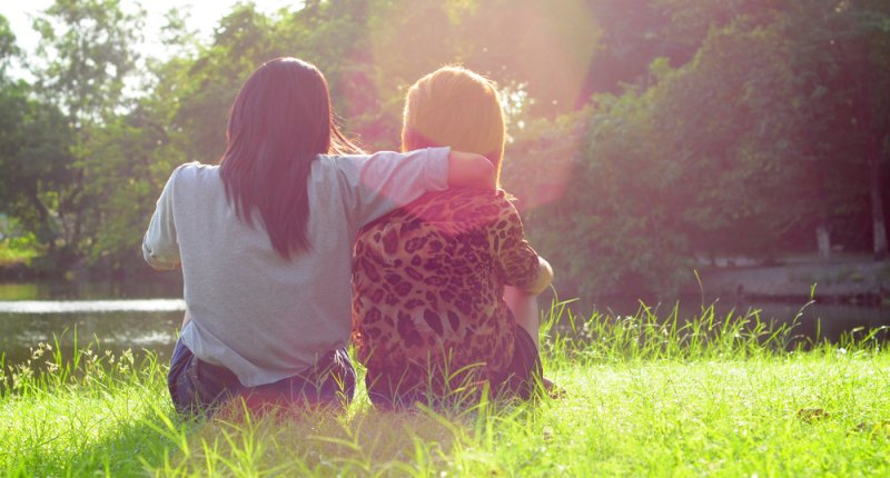 A lesbian couple sitting in a sunny field (Shutterstock.com)