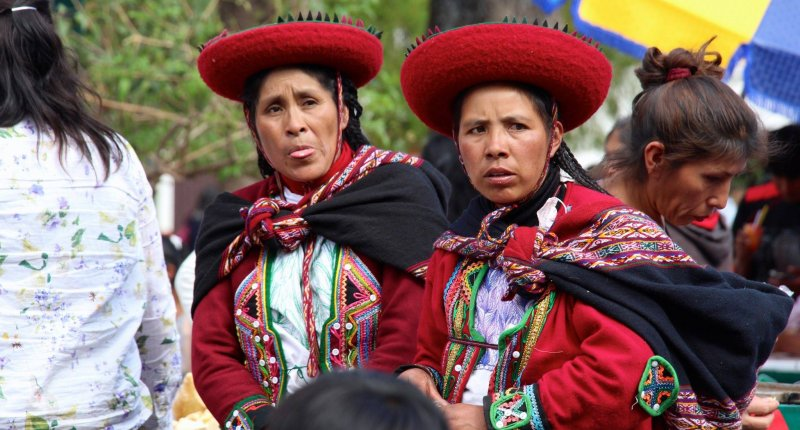 Two women dressed in traditional attire wait outside of city hall in Urubamba, Peru (Roxanne Cooper)