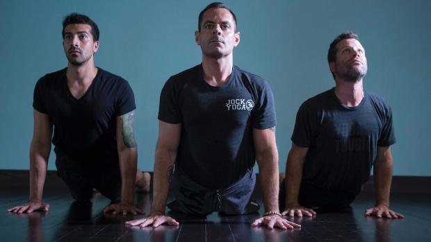 Michael DeCorte, centres, adopts an upward dog pose alongside Salmaan Sayeed, left, and Howie Track at Toronto's Moksha Yoga studio. (Chris Young/The Canadian Press)