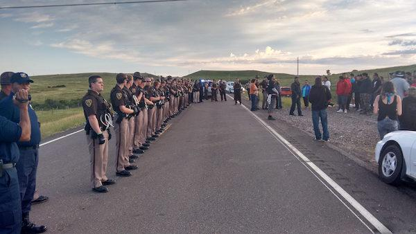Courtesy Standing Rock Dakota Access Pipeline Opposition Police line up before protesters near the construction site of the Dakota Access oil pipeline.