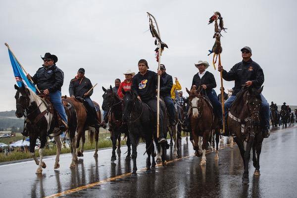 The Chief Big Foot Riders arriving in camp to support their Hunkpapa relatives. The riders honor the memory Mniconjou Lakota Chief Bigfoot and his band of 400 people who were massacred at Wounded Knee Creek by the U.S. Army 7th Calvary. In December 1990, they began a four-year commemoration on horseback over the same trail that Chief Big Foot's band followed in 1890, paying tribute and mourning those that died 100 years ago. Credit: Thosh Collins.