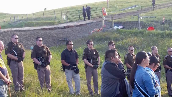 Officers removed their hats out of respect as a Lakota prayer song is sung as part of morning prayers at the site where construction was halted by water protectors. (Photo: Courtesy No Dakota Access Pipeline).