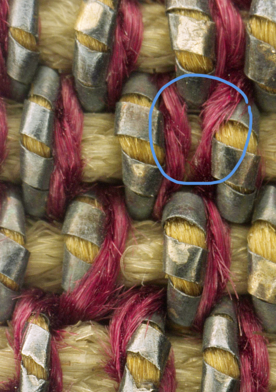 The decorative vertical threads include both crimson colored silk wefts as well as precious metal weft threads.