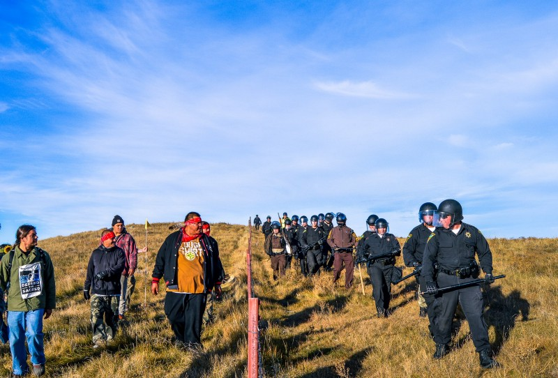 Protestors face off with the Riot Police across the fenceline near a Dakota Access construction site. CREDIT: Facebook/Rob Wilson.