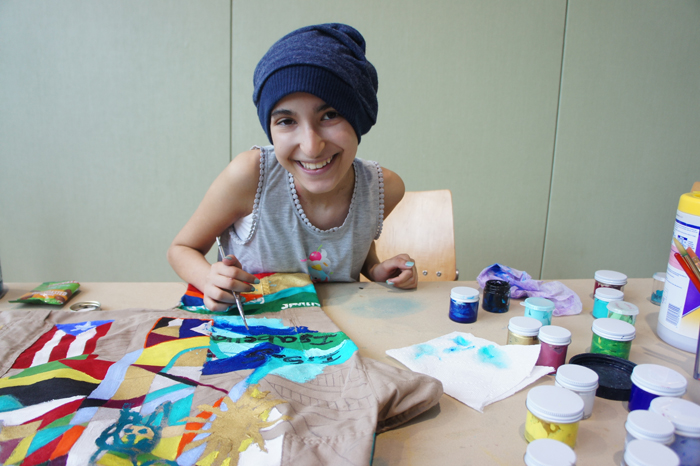 A patient decorating COURAGE with acrylic paint.