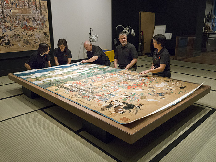 Conservators working on Hanabusa Itchō's 'Death of Buddha.' All photos courtesy of MFA Boston.