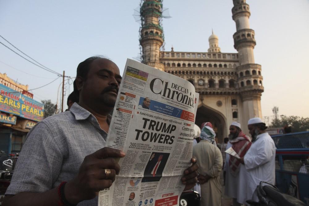 An Indian man reads news of Trump's election. CREDIT: AP Photo/Mahesh Kumar A.