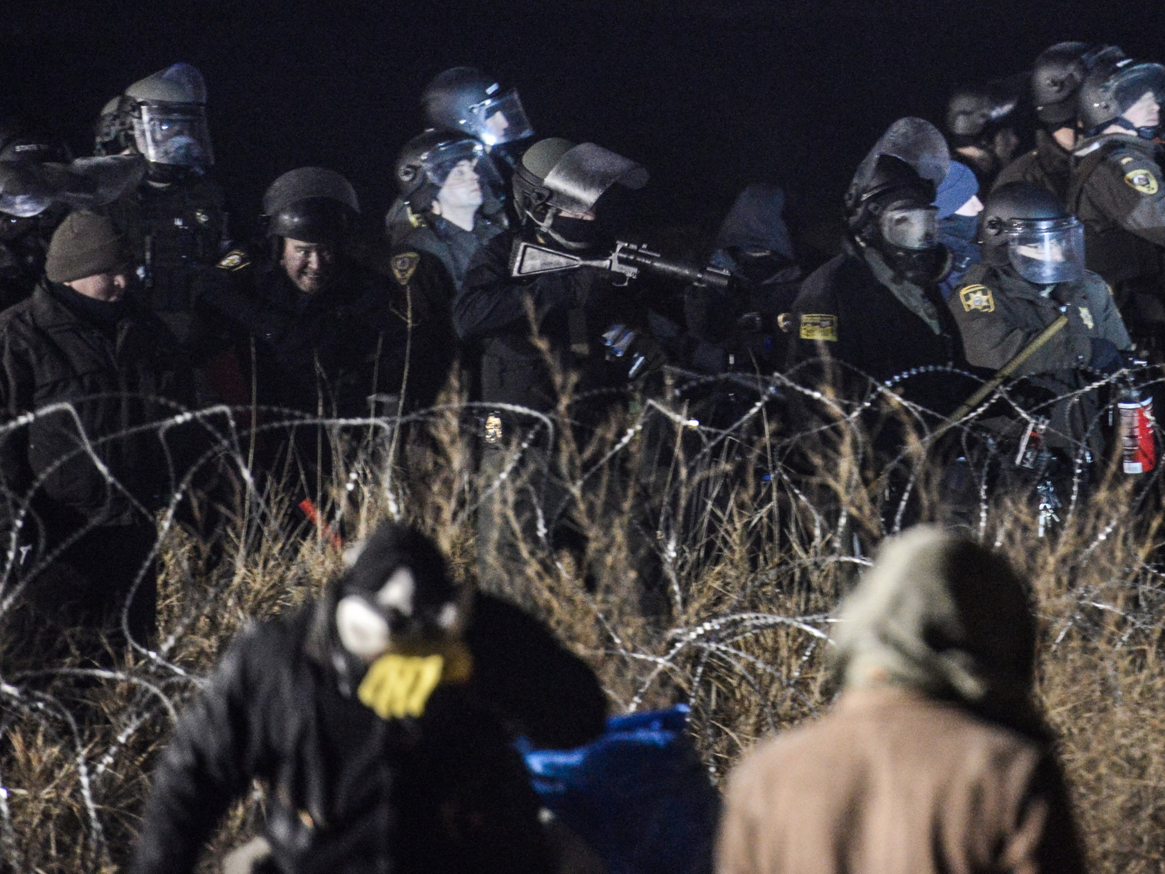 Police confront protesters with a rubber bullet gun during a protest against plans to pass the Dakota Access pipeline near the Standing Rock Indian Reservation, near Cannon Ball, North Dakota, U.S. November 20, 2016. Stephanie Keith/REUTERS
