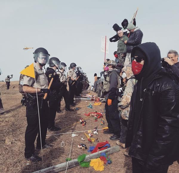 Courtesy Dallas Goldtooth/Indigenous Environmental Network A line of prayers and police facing off at construction site of the Dakota Access Pipeline. The takeaway: Stay peaceful, and stand firm.