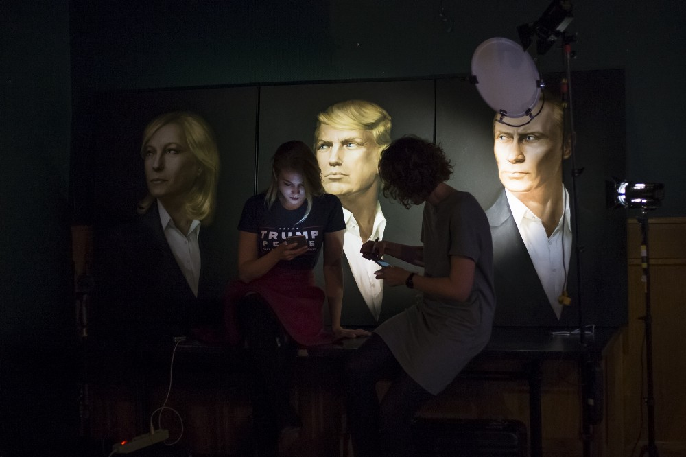 Two women look at their cell phones in front of portraits of U.S. President-elect Donald Trump and Russian President Vladimir Putin, right, as they arrive at the Union Jack pub in Moscow, Russia, to watch a live telecast of the U.S. presidential election on Wednesday, Nov. 9, 2016. CREDIT: AP Photo/Alexander Zemlianichenko.