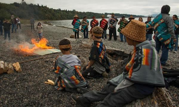 Members of the Lummi Nation burn a symbolic check in protest of the proposed Gateway Pacific coal export terminal in 2012. The terminal was eventually defeated when the U.S. Army Corps of Engineers ruled that the project would impact the Lummi Nation's fishery at Cherry Point, which is protected under the 1855 Treaty of Point Elliott. Credit: Paul Anderson.