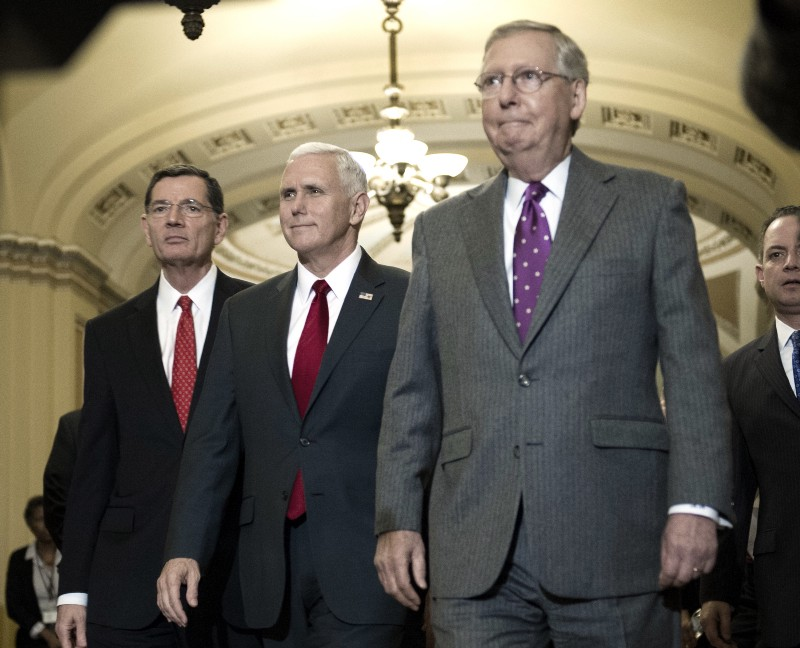 Vice President-elect Mike Pence, flanked by Senate Majority Leader Mitch McConnell and Sen. John Barrasso CREDIT: AP Photo/Cliff Owen.