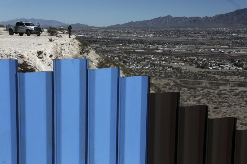 An agent of the border patrol, observes near the Mexico-US border fence, on the Mexican side, separating the towns of Anapra, Mexico and Sunland Park, New Mexico, on January 25. CREDIT: AP Photo/Christian Torres.