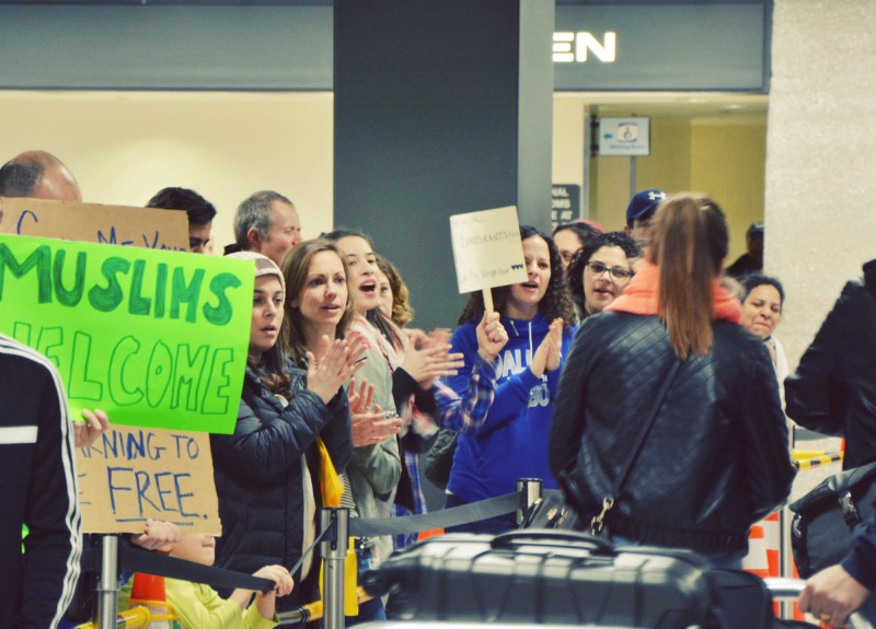 A crowd welcomes passengers as they exit customs at Dulles International Airport in Virginia. CREDIT: Jack Jenkins/ThinkProgress.