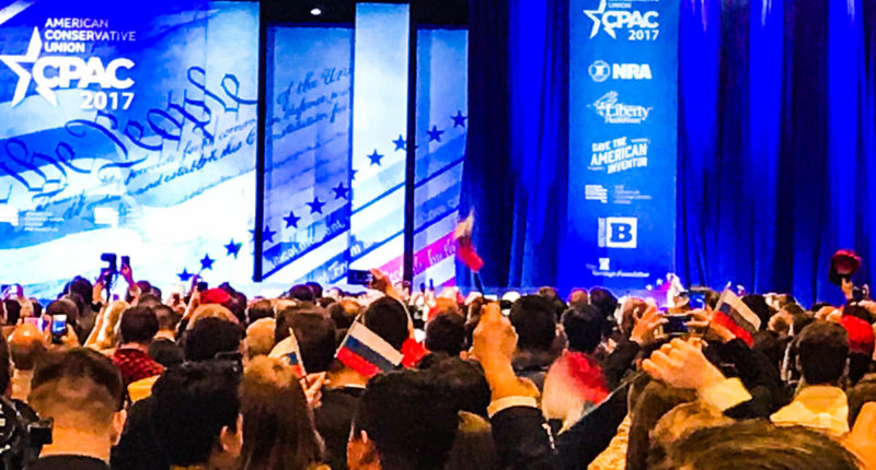 """CPAC attendees wave Russian flags with the word """"TRUMP"""" written on the front (Screen cap)."""