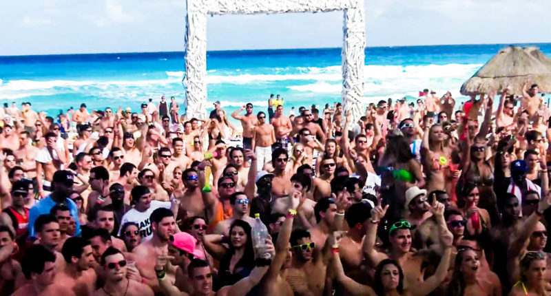 Students party on a beach in Cancun (Screen cap).
