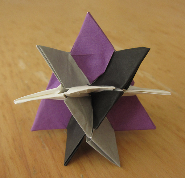 Four intersecting triangles, in the colors purple, white, gray, black