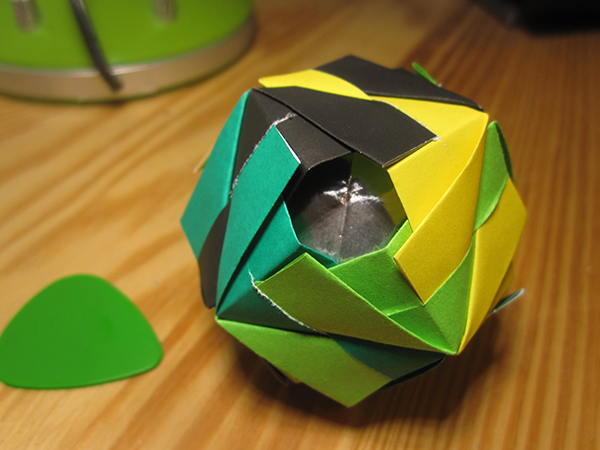 The Etna Kusudama model. The shape symmetry group is that of a cube, and a single face of the cube is facing the camera. The four edges around that face are colored black, yellow, light green, dark green.