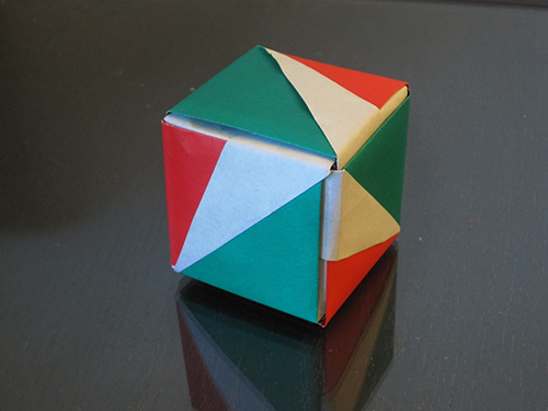 A cube. Three faces are showing, and they're colored in a symmetrical way so that the faces can be rotated into each other without changing their colors.
