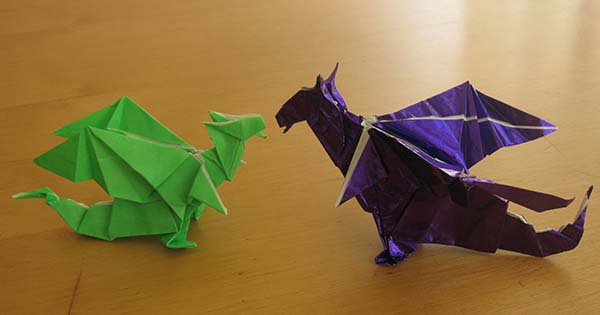 two dragons, one smaller green one and larger purple one, looking at each other