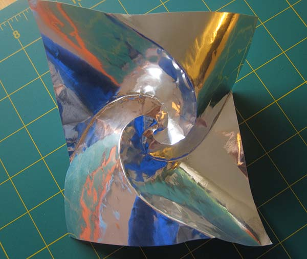 A square sheet of silver foil paper, with 4 spiral creases radiating from the center