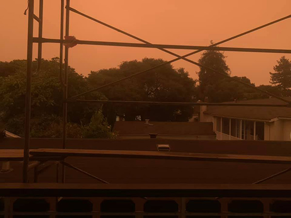 photo of orange sky, as seen from a balcony, with some scaffolding in the way
