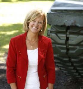 Jeanne Ives standing next to a tank