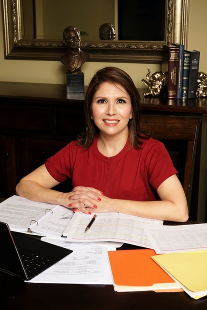 former Lt. Governor Evelyn Sanguinetti sitting at a desk covered with papers.