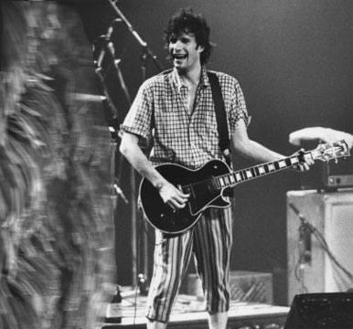 Paul Westerberg of The Replacements plays guitar while an alien stands next to him.