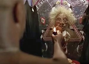 "Screenshot from the movie ""Major League"". A fit, shirtless man holds the flame of a lighter to a cigar in the mouth of a short wild-haired voodoo loa figurine in a locker."