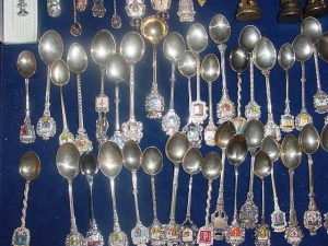 A collection of souvenir silver spoons with enamel coats of arms on their handles. Photo by Lourdes Cardenal via Wikimedia Commons.