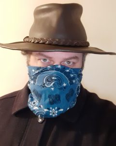 The image shows the author in his pandemic shopping outfit. He's wearing a dark navy blue wool jacket, a brown leather broadbrim hat, and a blue paisley bandanna covering his face below his eyes.