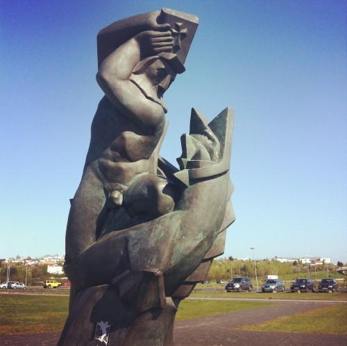 A statue at the University of Iceland of a man smacking a devil/seal with a bible