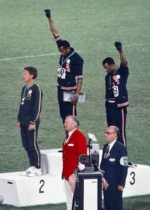 American sprinters Tommie Smith and John Carlos, along with Australian Peter Norman, during the award ceremony of the 200 m race at the Mexican Olympic games. During the awards ceremony, Smith (center) and Carlos protested against racial discrimination: they went barefoot on the podium and listened to their anthem bowing their heads and raising a fist with a black glove. Mexico City, Mexico, 1968.