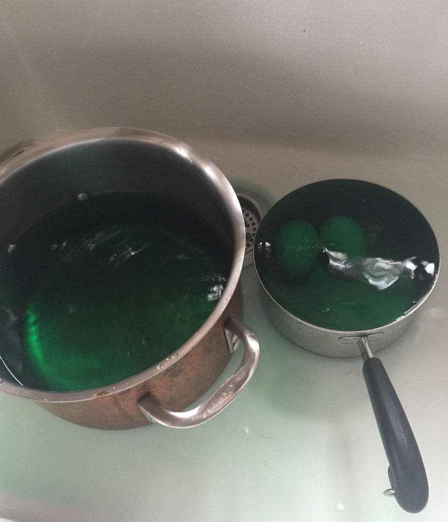 eggs in pan with green dye, cooling